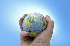 World in your hand. Shot of mans hand holding a toy globe. The shot has been  using a snooted strobe to brighten the background. No sharpening has been applied Royalty Free Stock Image
