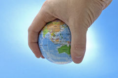 World in your hand. Shot of mans hand holding a toy globe. The shot has been  using a snooted strobe to brighten the background. No sharpening has been applied Royalty Free Stock Photos