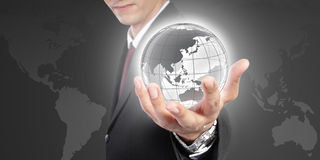 The world is in your hand. A conceptual business image. The world is in your hand. Conceptual image of global control, power and domination. A man in formal wear Royalty Free Stock Photo