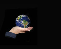 The World In Your Hands. Globe of the world gently held up in the palm of a woman's hand and on a black background with lots of copyspace Royalty Free Stock Photo