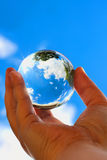 World in your hands. Hand holding a glass ball reflecting trees against a blue sky Royalty Free Stock Images