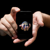 The world in your hands, smartphone. (on black, very shallow depth of field Royalty Free Stock Photos