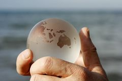 World is your oyster. Man holding a crystal globe of the earth in his hands with Oceania and Australia prominent with the ocean in the back ground royalty free stock images