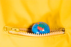 The world in your pocket. Small globe in the zipped pocket (The World in Your Pocket concept Stock Images