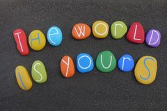 The world is yours, motivational words of wisdom composed with multi colored stones over black sand. Motivational phrase, the world is yours, composition with vector illustration