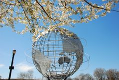The Worlds Fair Globe framed by Cherry Trees and blue sky Stock Photo