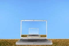 Worlds Within Worlds. Silver laptop with the lid open against a hillside of rough stubble grass against a clear blue sky, with the whole image also mirrored Royalty Free Stock Photo