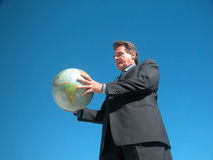 Worldwide Access. Man holding globe with both hand and looking at it Royalty Free Stock Images