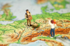 Worldwide Courier Service. A tiny miniature figurine of a man carrying a parcel across a map to a waiting recipient, macro concept royalty free stock images