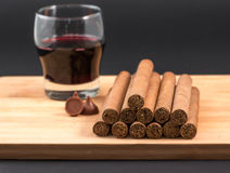 Worldwide famous hand rolled Cuban cigars with Red Wine. Worldwide famous Cuban cigars over wood with chocolates and coffee, hand rolled natural habanos an Stock Images