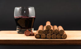Worldwide famous hand rolled Cuban cigars with Red Wine. Worldwide famous Cuban cigars over wood with chocolates and wine, hand rolled natural habanos an Royalty Free Stock Photography