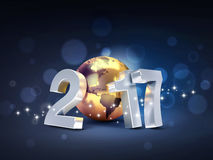 2017 Worldwide greeting symbol. 2017 New Year type composed with a golden planet earth, on a sparkling black background - 3D illustration Stock Images