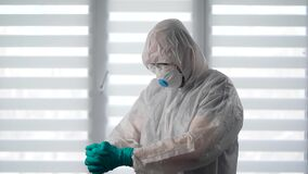 Pandemic Covid-19. Portrait of a virologist in a protective suit. A male epidemiologist is ready to fight the infection.