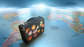 Worldwide travel. Vintage suitcase over map of the world Royalty Free Stock Images