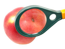 Worm-eaten apple under magnifying glass. Stock Photos