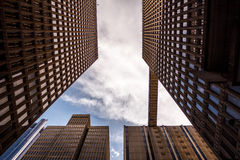 Worm's Eye View of City Buildings Under Sunny Cloudy Sky Stock Photos