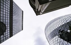 Worm's Eye View of Mirror Covered Concrete Buildings Under Gray Cloudy Skies Stock Photography