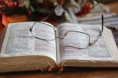 Worn открытая библия с стеклами Стоковое Изображение