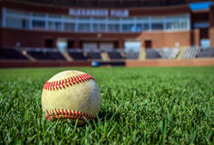 Worn Baseball on Baseball Stadium. A worn baseball on a baseball field in a stadium Stock Photos