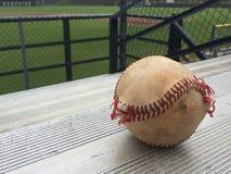 Worn baseball in corner of bleachers stock image