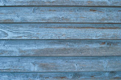 Worn blue board siding. Worn blue boards on the side of a shed royalty free stock photos