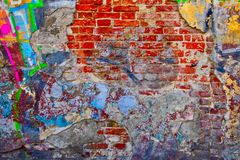 Worn brick wall half plastered with many layers of aged stucco stock photo