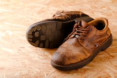 Worn brown leather boots on OSB board Stock Photo