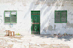 Worn building facade with green shutters Stock Photo