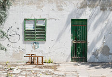 Worn building facade with green shutters Royalty Free Stock Image
