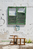 Worn building facade with green shutters Stock Photography