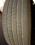 Worn Car Tire with Irregular Used Bald Low Thread. Irregular worn automobile car tire showing bald edge and low used thread Stock Photo