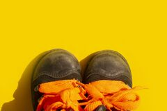 Worn children`s black shoes with orange laces on a yellow background