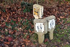 Worn concrete British UK Stop Valve and Hydrant signs on leaf covered ground royalty free stock photo