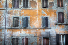 Worn down building with window shutters. Royalty Free Stock Image