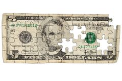 Worn Five dollar bill. Cut out into puzzle shapes isolated over white Royalty Free Stock Photo