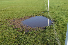 Worn football goalmouth with water Royalty Free Stock Photography