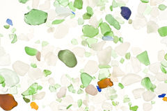 Worn glass. From a beach scattered on a white background Stock Photos