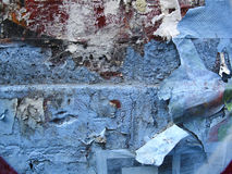 Worn graffiti. Old brick wall with graffiti and parts of old posters peeling off Royalty Free Stock Images