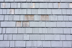 Worn gray stained cedar shingles. Rows of gray stained cedar shingles with several shingles showing age by peeling from weather Royalty Free Stock Images