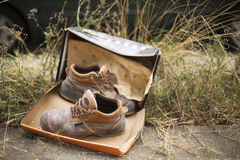 Worn hiking boots with box in grassland. A pair of old, battered walking boots are placed on a rock in the veld. Shot with Canon EOS 5D Mark 3 Stock Images