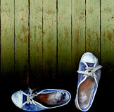 Worn jeans gym shoes against a wooden plank wall Royalty Free Stock Image