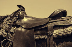Worn leather western horse saddle. A sepia toned photo of a leather saddle on a horse Royalty Free Stock Photo