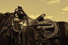 Worn leather western horse saddle. A sepia toned photo of a leather saddle on a horse Stock Image