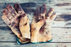 Worn leather work gloves on wood background, stained with grease and industrial oil royalty free stock photography