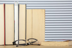 Worn looking reading books on a table with eye glasses. Worn looking reading books upright on a table with eye glasses laying in front of them stock image