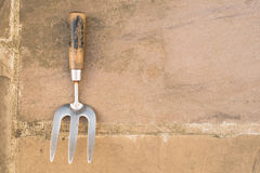 Worn metal and wooden garden hand fork. On some patio paving slabs Royalty Free Stock Photography