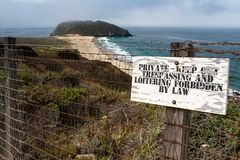 A worn no trespassing sign in front of a fence topped with barbed wire, in the background a beautiful sandy beach and the crashing stock photo
