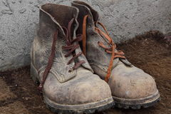 Worn old boots. With different shoelaces, scuffed and dirty leather Royalty Free Stock Image