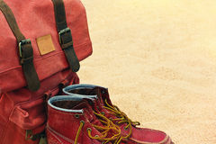 Worn old boots and retro rucksack on a beach Royalty Free Stock Photos
