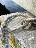 Worn old rope tied to the bottom of a bridge royalty free stock photography